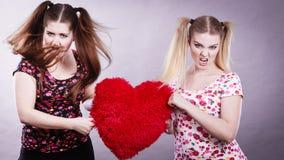 Deux femmes agressives ayant discutent le combat tenant le coeur Image libre de droits