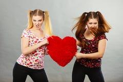 Deux femmes agressives ayant discutent le combat tenant le coeur Photo libre de droits