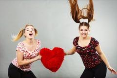 Deux femmes agressives ayant discutent le combat tenant le coeur Photographie stock