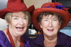 Deux femmes aînés utilisant les chapeaux rouges Image stock
