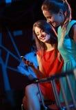 Deux femmes appréciant avec un smartphone Photo libre de droits