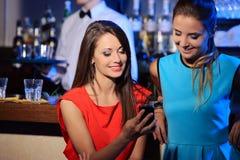 Deux femmes appréciant avec un smartphone Image stock