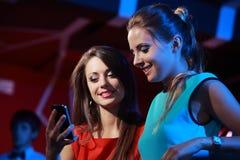 Deux femmes appréciant avec un smartphone Photos libres de droits