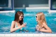 Deux femmes appréciant des vacances d'été avec des cocktails par la piscine images libres de droits