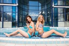 Deux femmes appréciant des vacances d'été avec des cocktails par la piscine image libre de droits
