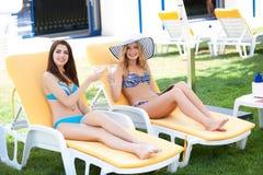 Deux femmes appréciant des vacances d'été avec des cocktails par la piscine photographie stock