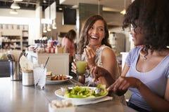 Deux femmes appréciant la date de déjeuner dans le restaurant d'épicerie fine Images stock