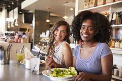 Deux femmes appréciant la date de déjeuner dans le restaurant d'épicerie fine Image libre de droits