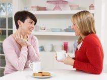 Deux femmes appréciant la boisson chaude dans la cuisine Photo libre de droits