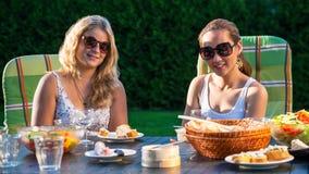 Deux femmes appréciant la réception en plein air Image stock