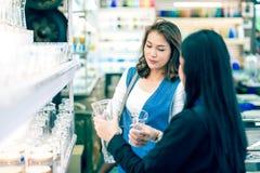 Deux femmes asiatiques choisissant et achetant des verres dans la cuisine font attention au sho image stock