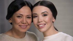 Deux femmes asiatiques de sourire regardant le plan rapproché de visages d'appareil-photo, de mère et de fille banque de vidéos