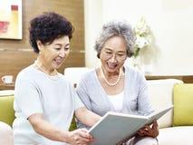 Deux femmes asiatiques supérieures lisant un livre ensemble Photo stock