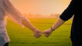 Deux femmes asiatiques utilisant les chemises blanches et noires se tiennent soient la main i Photo stock