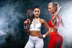 Deux femmes athlète et joueurs de tennis sur le fond noir Concept de sport et de tennis photos stock