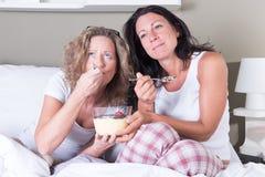 Deux femmes attirantes appréciant la soirée de leurs femmes dans le lit Photographie stock
