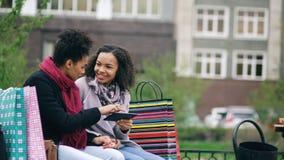 Deux femmes attirantes de métis avec des paniers se reposant sur le banc et à l'aide de la tablette pour le surfing sur Internet Image stock