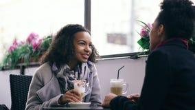 Deux femmes attirantes de métis parlant et buvant du café en café de rue Les amis ont l'amusement après vente de visite de mail Image libre de droits