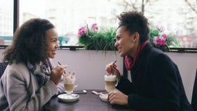 Deux femmes attirantes de métis parlant et buvant du café en café de rue Les amis ont l'amusement après vente de visite de mail Photos stock
