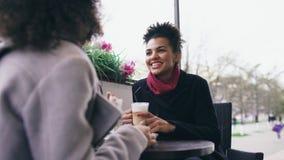 Deux femmes attirantes de métis parlant et buvant du café en café de rue Les amis ont l'amusement après vente de visite de mail Images libres de droits