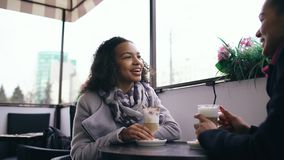 Deux femmes attirantes de métis parlant et buvant du café en café de rue Les amis ont l'amusement après vente de visite de mail Photographie stock libre de droits