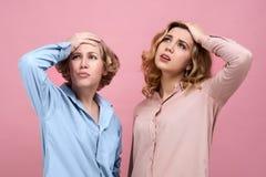 Deux femmes attirantes se tiennent sur leurs têtes avec une expression frustrante sur leurs visages La perte et l'échec les ont p Photos libres de droits
