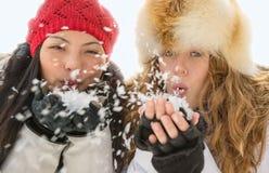 Deux femmes attirantes soufflant la neige en hiver Photos stock