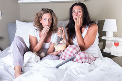 Deux femmes attratcive s'asseyant dans le lit et regardant un film effrayant Image stock