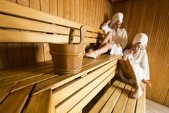 Deux femmes au bien-être et au centre de station thermale détendant dans le sauna en bois Image libre de droits
