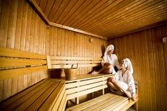 Deux femmes au bien-être et au centre de station thermale détendant dans le sauna en bois Photo libre de droits