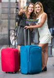 Deux femmes avec des bagages vérifiant l'itinéraire dehors Photo stock