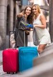 Deux femmes avec des bagages vérifiant l'itinéraire dehors Photographie stock