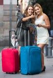 Deux femmes avec des bagages vérifiant l'itinéraire dehors Image stock