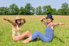 Deux femmes avec des chapeaux saluant dans le pâturage vert Image stock
