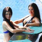 Deux femmes avec des cocktails dans la piscine Photographie stock libre de droits