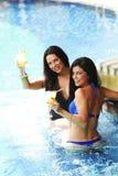 Deux femmes avec des cocktails dans la piscine Images libres de droits