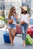Deux femmes avec des valises sur le chemin à l'aéroport Images stock