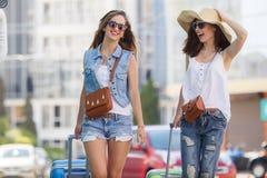 Deux femmes avec des valises sur le chemin à l'aéroport Image stock