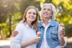 Deux femmes avec du charme de sourire ayant une promenade avec la crème glacée  Image stock