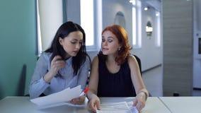 Deux femmes avec du charme discutent la conclusion de détails du traité clips vidéos