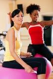 Deux femmes avec la bille de forme physique en gymnastique Image libre de droits