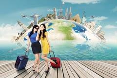 Deux femmes avec la valise et le point de repère du monde Images libres de droits