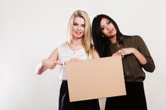 Deux femmes avec le conseil vide Photos stock