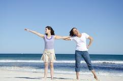 Deux femmes ayant l'amusement à la plage Photo stock