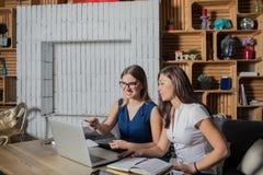 Deux femmes ayant la consultation, utilisant l'ordinateur portable photographie stock libre de droits