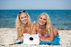 Deux femmes blondes ayant l'Internet surfant d'amusement sur la plage en été Images stock