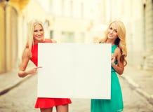 Deux femmes blondes heureuses avec le conseil blanc vide Photographie stock
