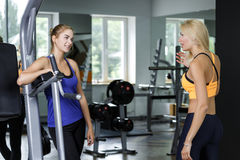 Deux femmes blondes sportives parlant dans le gymnase La fille communique avec l'entraîneur Images stock