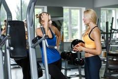Deux femmes blondes sportives parlant dans le gymnase La fille communique avec l'entraîneur Images libres de droits