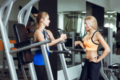 Deux femmes blondes sportives parlant dans le gymnase La fille communique avec l'entraîneur Photo stock